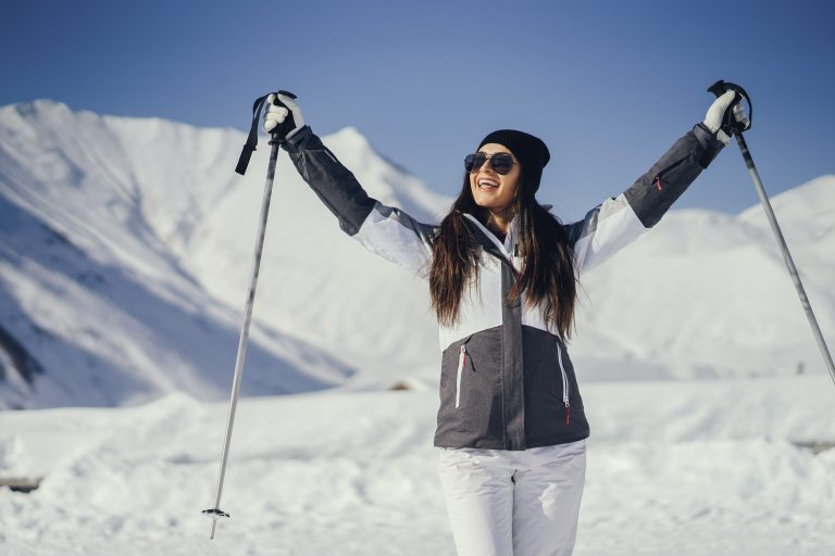 young and active brunette skiing in the snowy mountains