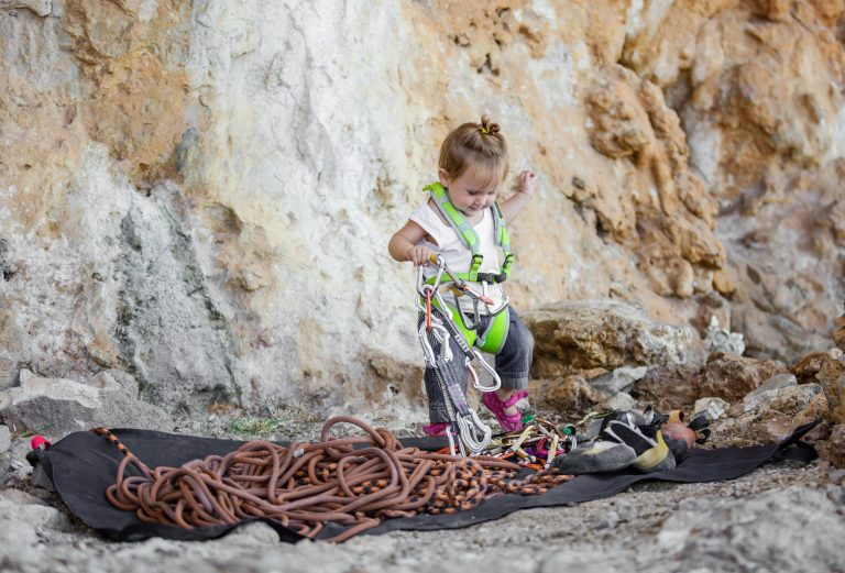 Little girl wearing safety harness and playing with rock climbing equipment